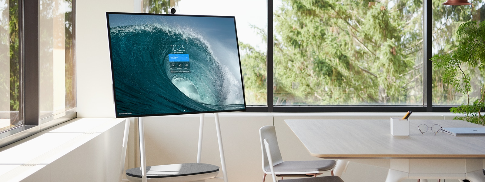 A Surface Hub 2 sits on a mobile stand and displays a start screen in a conference room.