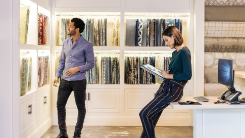 Man and woman in a design center looking at fabric samples