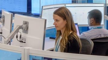 Ein Frau arbeitet an mehreren Bildschirmen in einem Datenzentrum