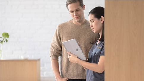 A healthcare professional looking at a tablet device with a person