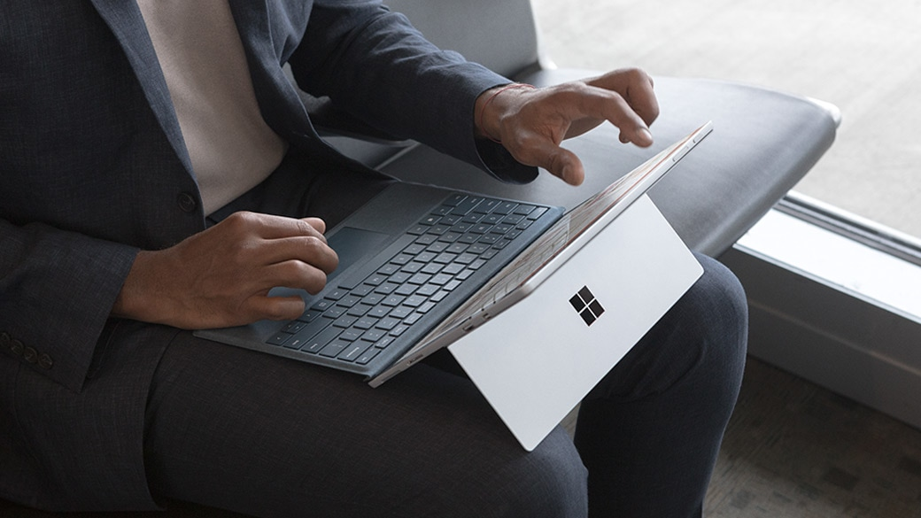 A person works in an airport lounge with a Surface Pro on their lap