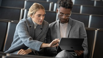 A man and woman looking at Surface Pro 6