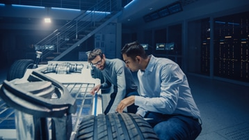 two business professionals viewing the underside of a vehicle