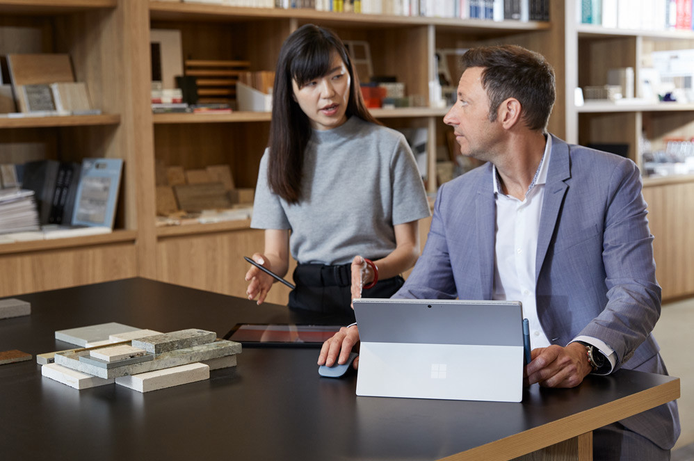 A man using a Surface Pro 7 turns to talk to his female colleague