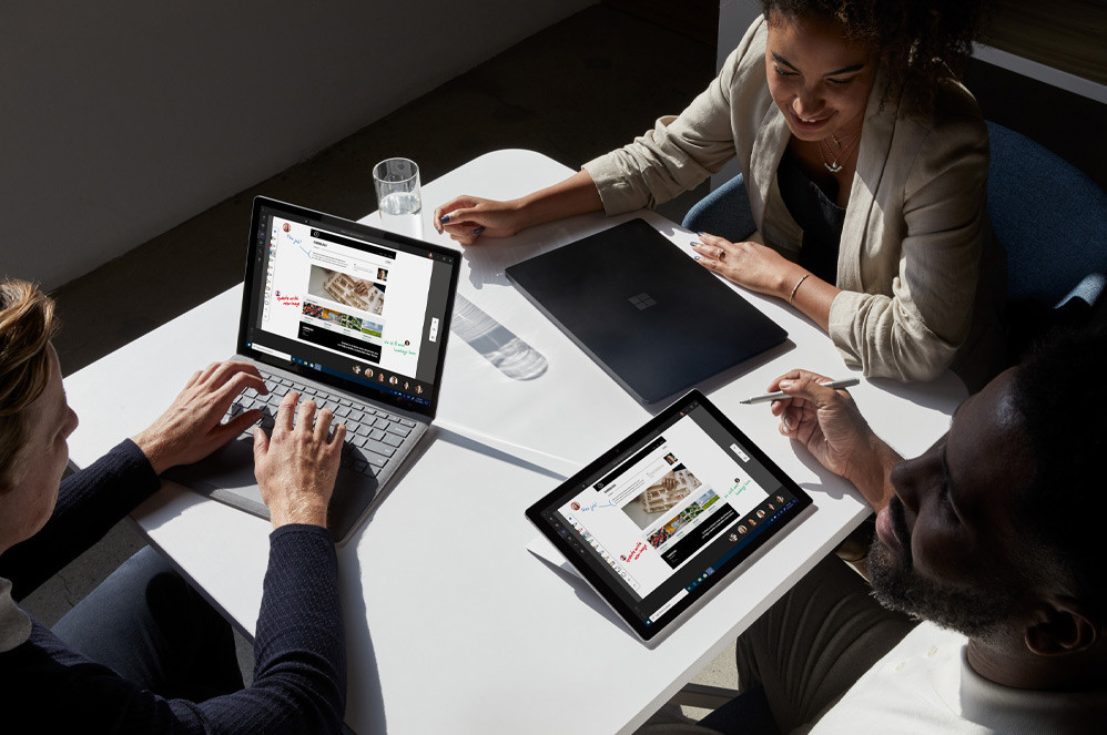 Three people sit together with their Surface devices at a small table