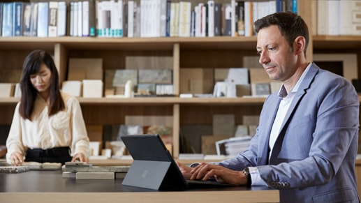 A man works in an open office with his Surface Pro 7