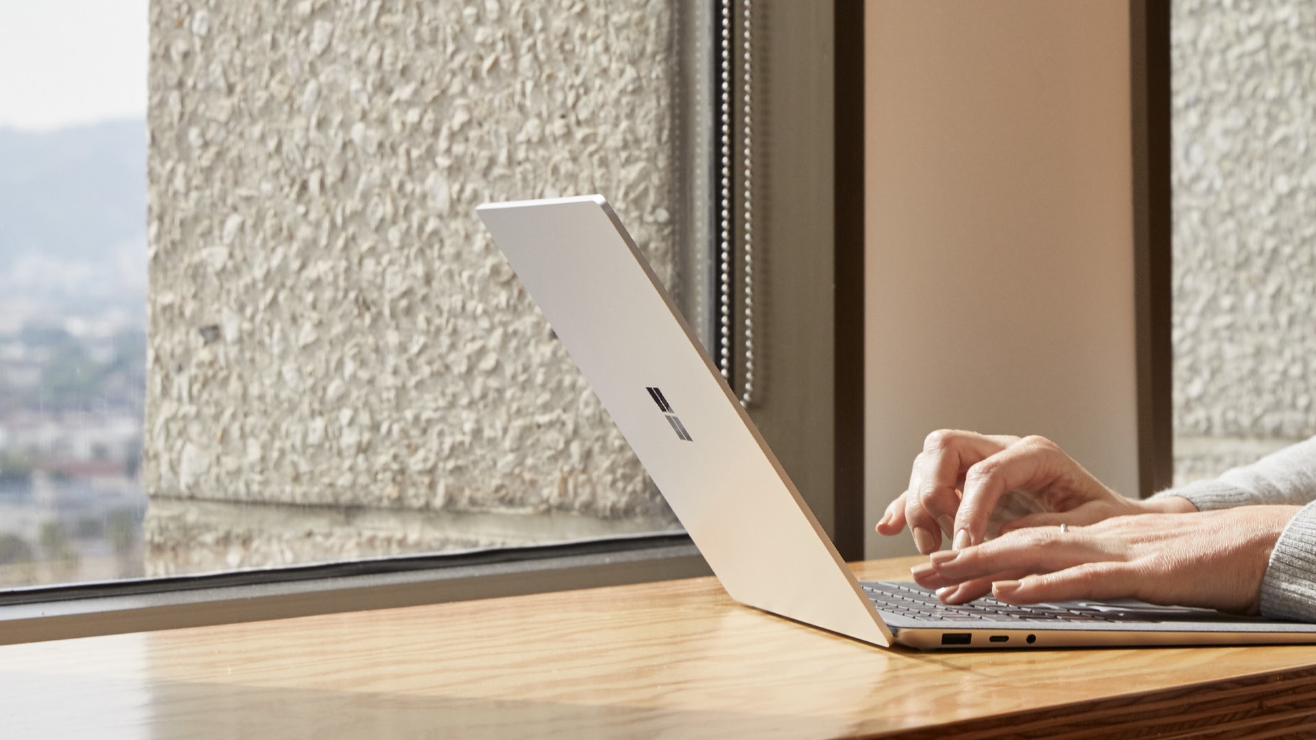A person works on their Surface Laptop 3 next to a window