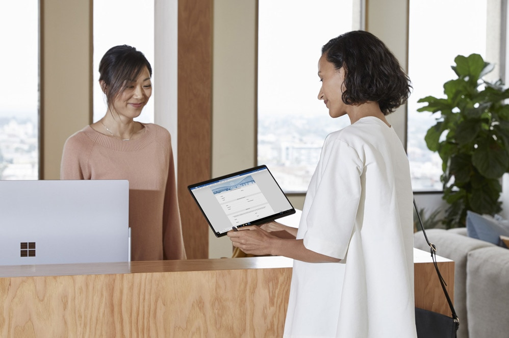 A woman at a reception desk uses a Surface Pro X