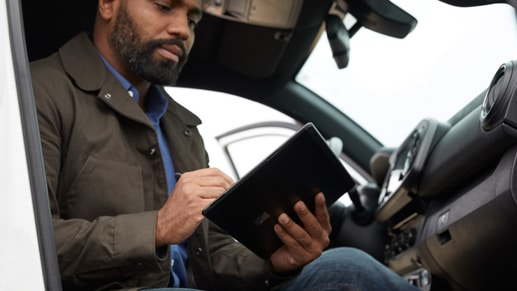 A man works on his Surface Pro X from the cab of his truck