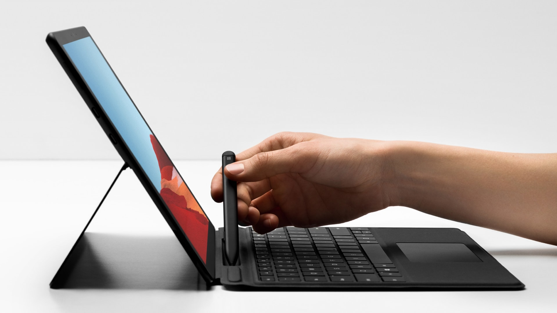A person reaches for Surface Slim Pen while using Surface Pro X and Surface Pro X Signature Keyboard