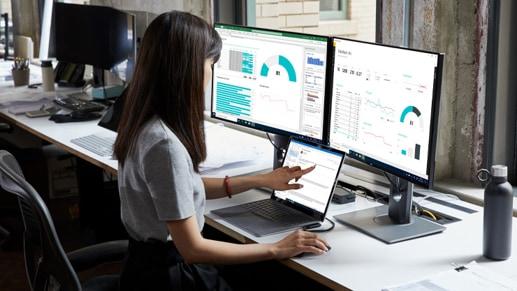 Женщина работает на своем ноутбуке Surface 3 за своим столом