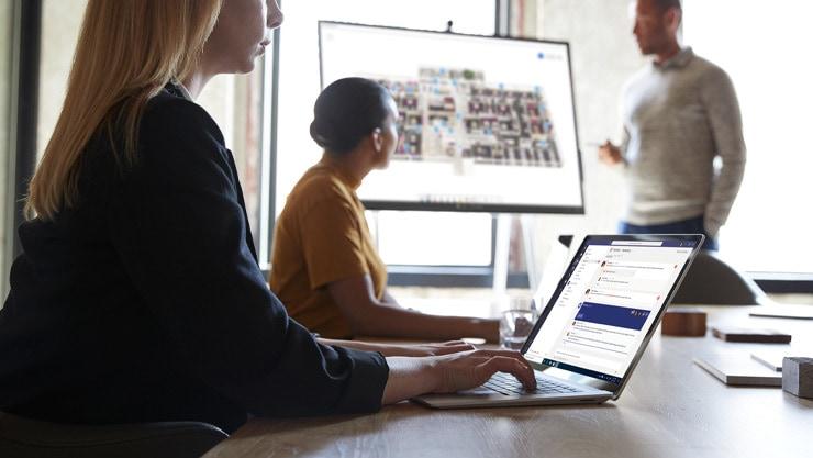 Женщина печатает на своем ноутбуке Surface 3 на встрече с коллегами