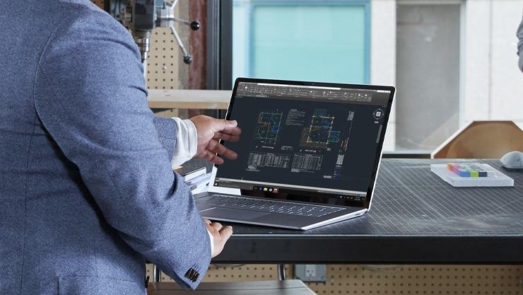 Человек взаимодействует с сенсорным экраном на своем ноутбуке Surface 3