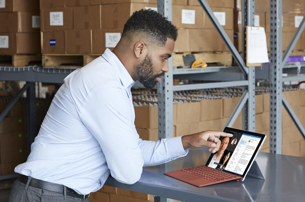 A man interacts with the touchscreen on his Surface Pro 7