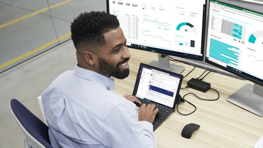 A smiling man types on his Surface Pro 7 in Laptop Mode