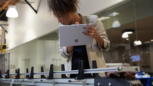 A woman holds her Surface Pro 7 In Tablet Mode and Inks with Surface Pen