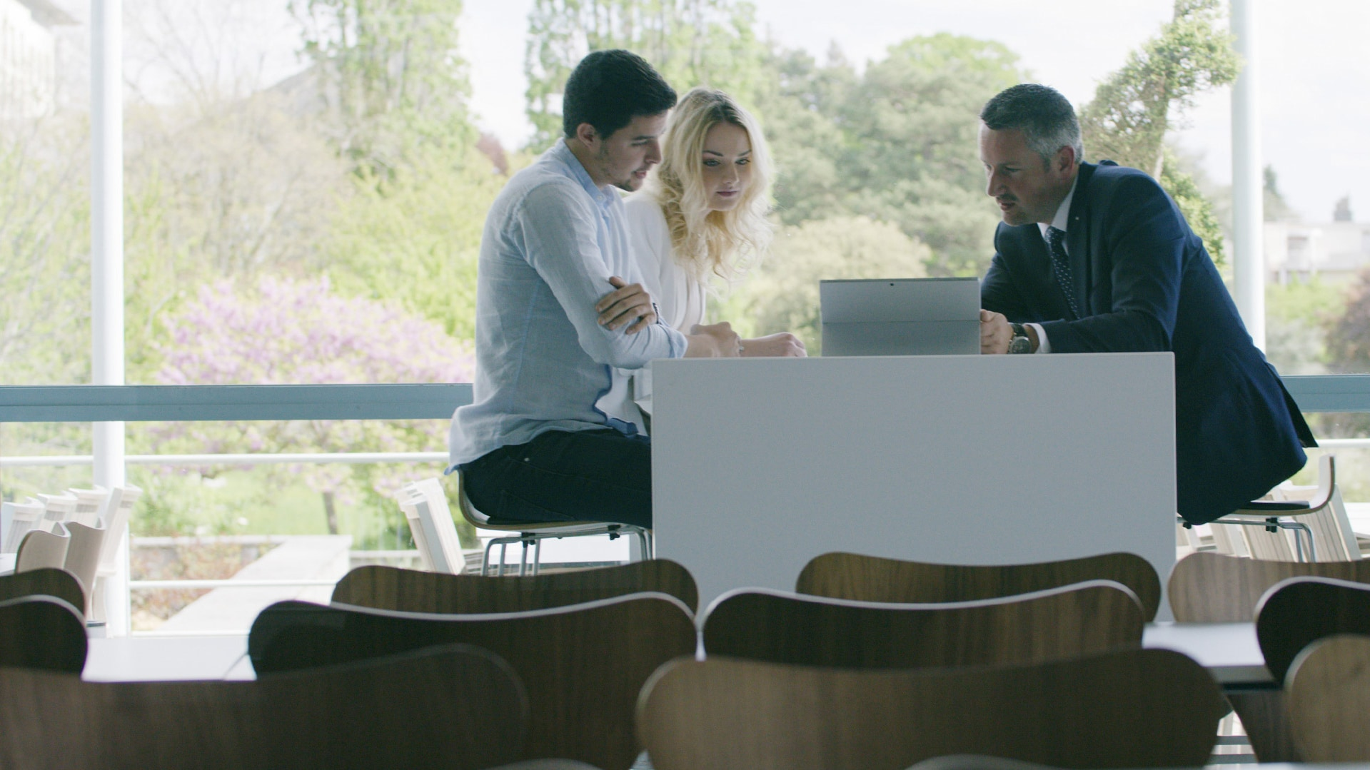 Customers meet with a Vaudoise representative who has a Surface Pro at his desk