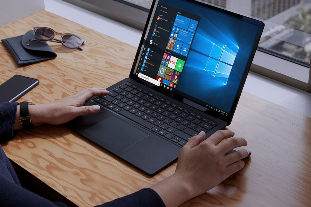 A person works on their Surface Laptop 3 with the Windows Start screen displayed