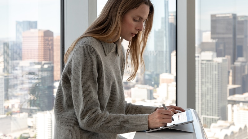 Photograph of a woman using the Surface Pen with the New Surface Pro 7