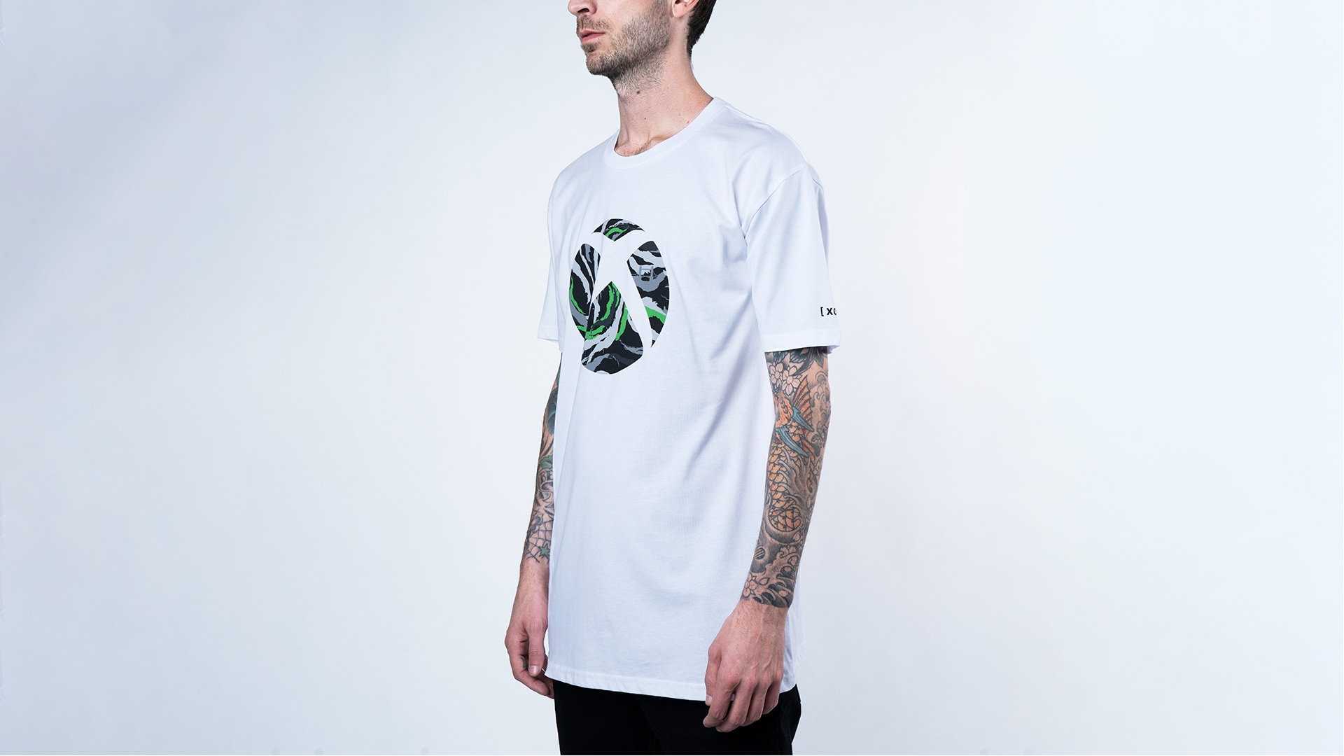 Un homme portant le t-shirt Sphère Xbox blanc