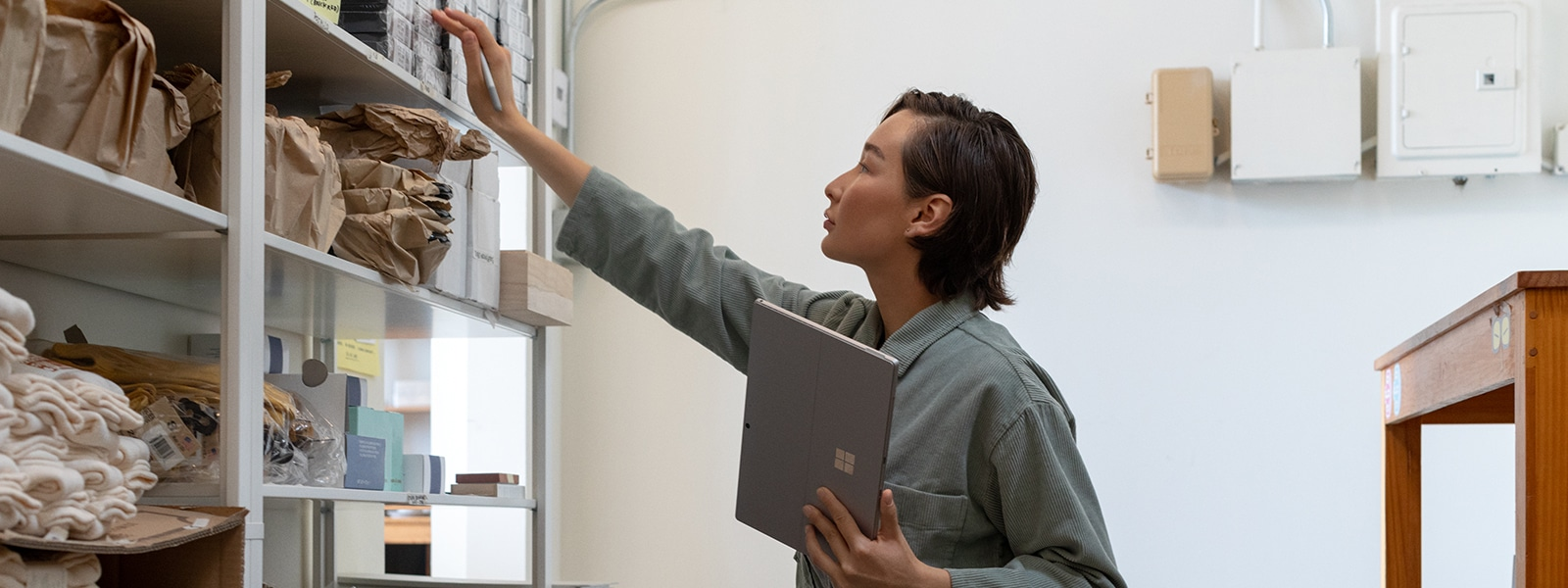 A woman holding a Surface Pro 7 while reaching for supplies on a shelf