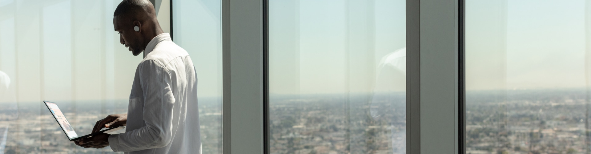 A person working on a laptop while standing by large windows with a view of the city below.