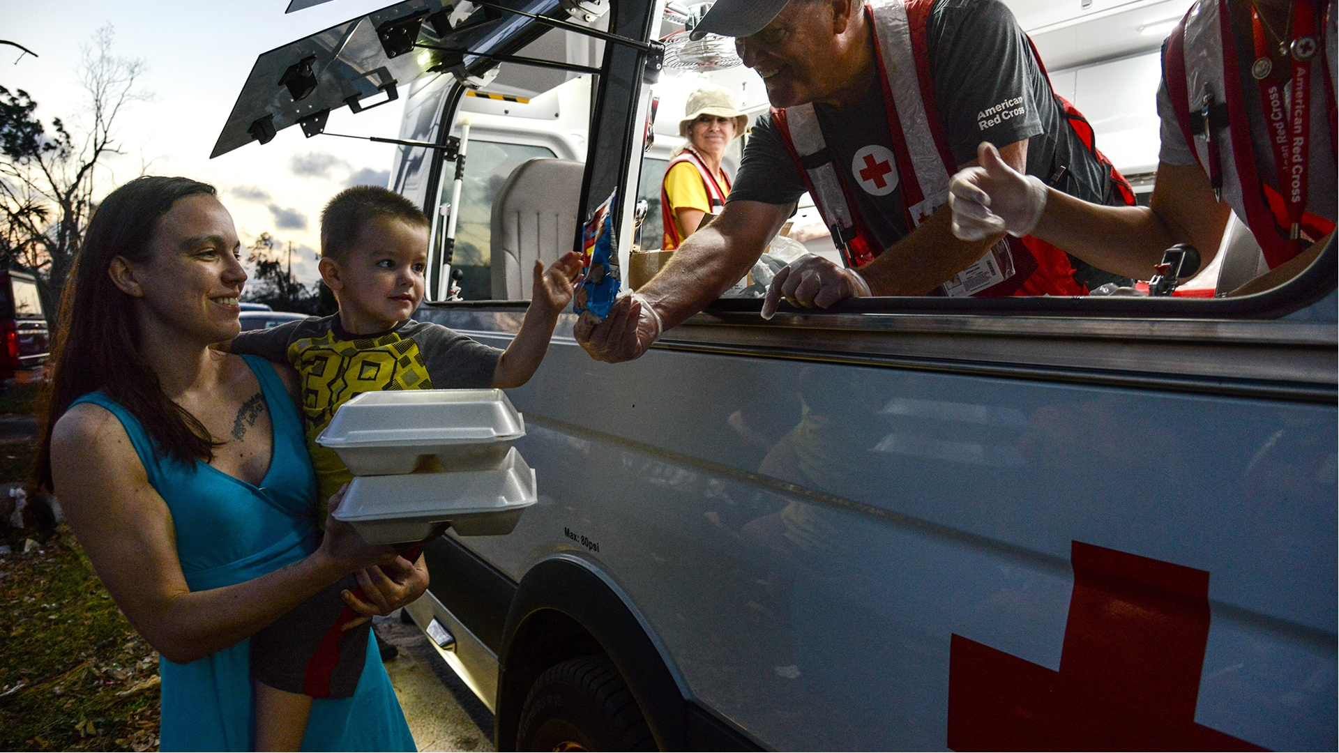 A Red Cross volunteer distributes food to a woman and a little boy