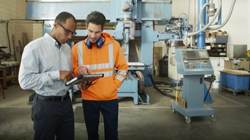 Zwei Männer im Außendienst schauen auf einen Tablet.