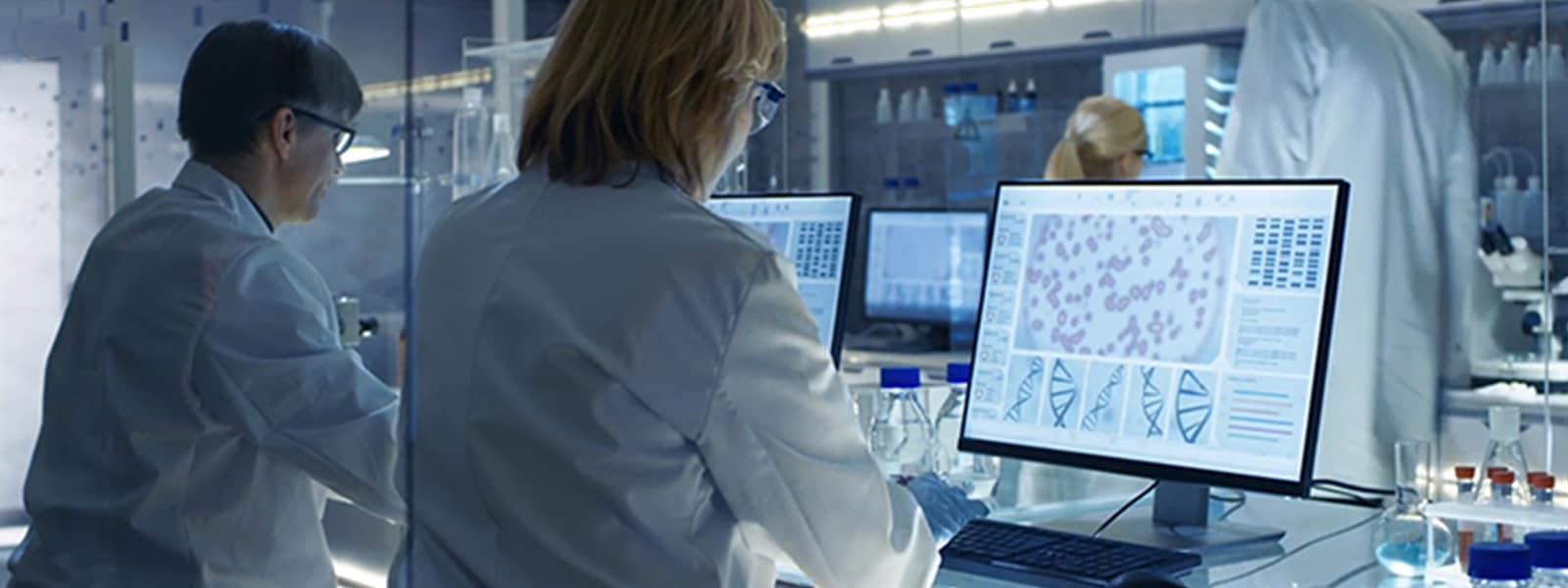 Technician works in front a screen displaying DNA sequences.