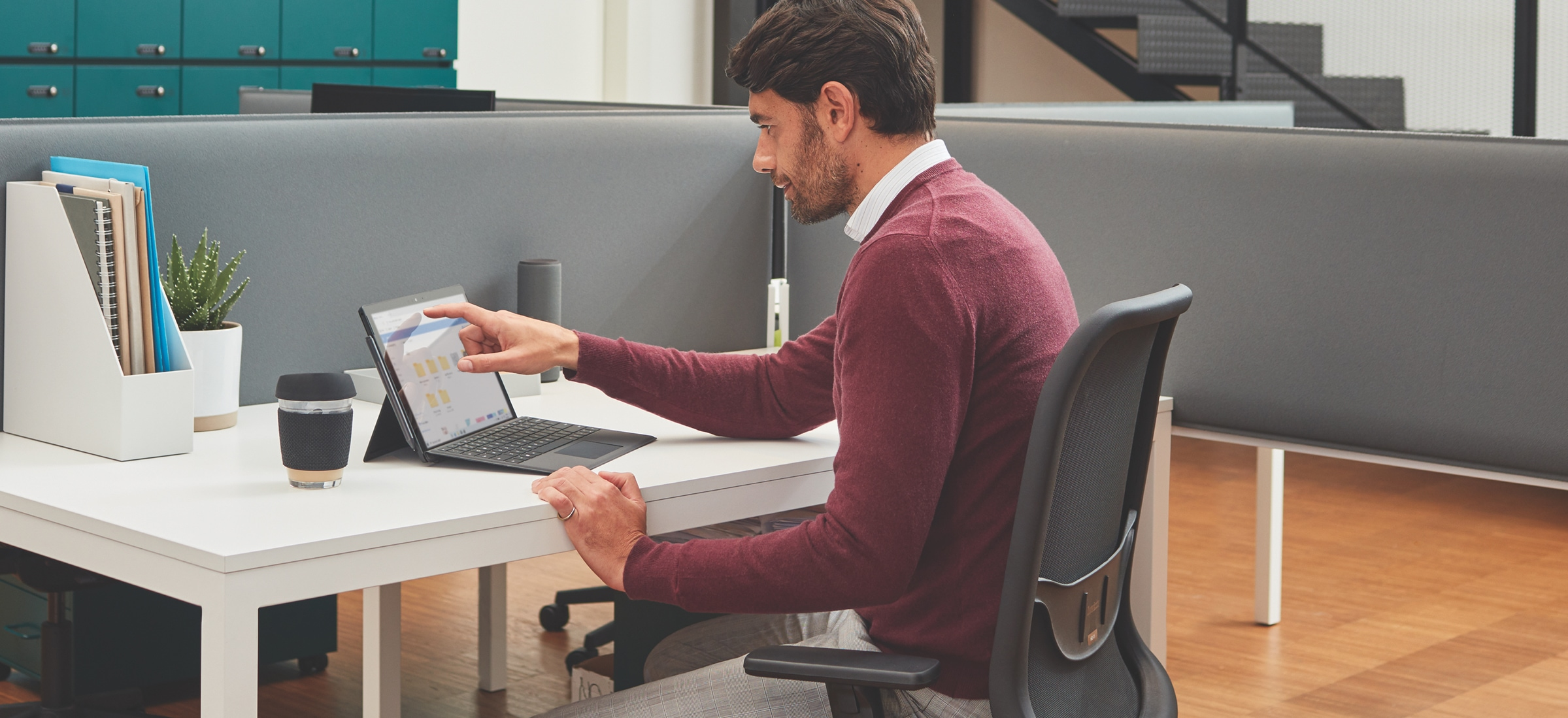Person seated at a cubicle desk in an office using a Microsoft Surface