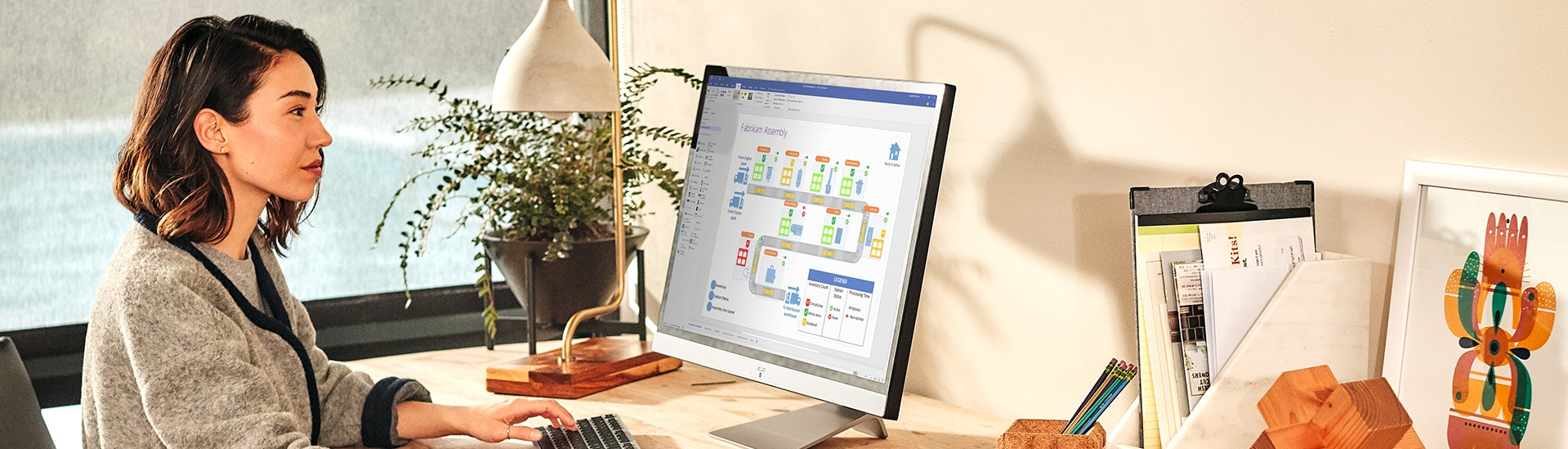 Photograph of a person looking at a file in Visio on a large desktop monitor
