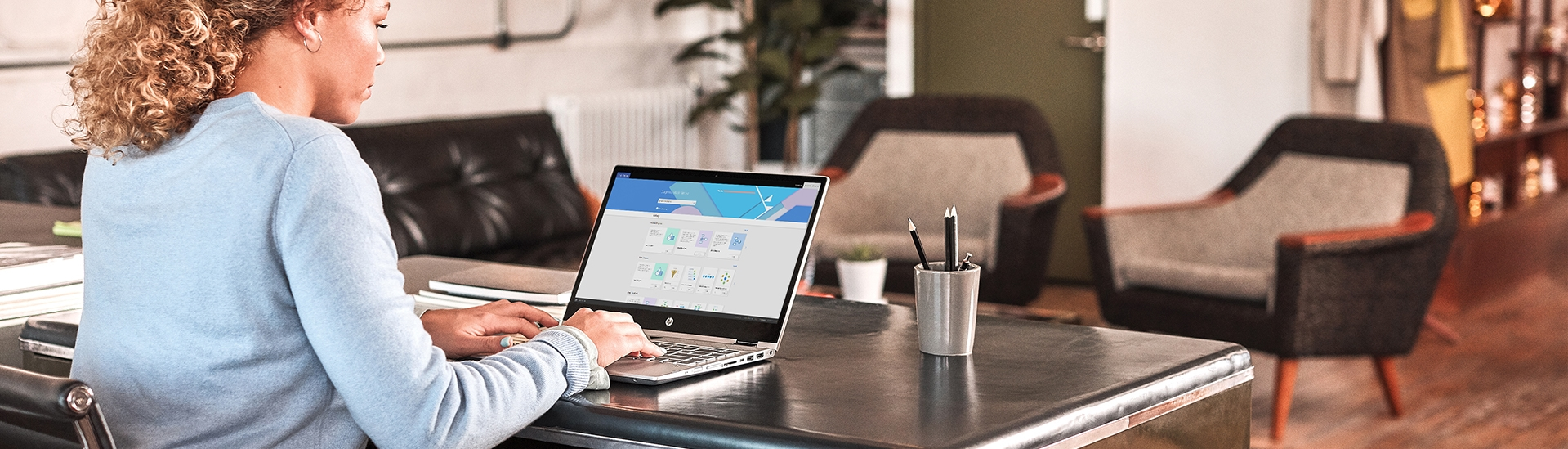 Photograph of a person working at desk and using a laptop
