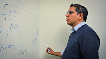 Paul Rojas looks at a whiteboard drawing of the Azure optimization recommendation platform.