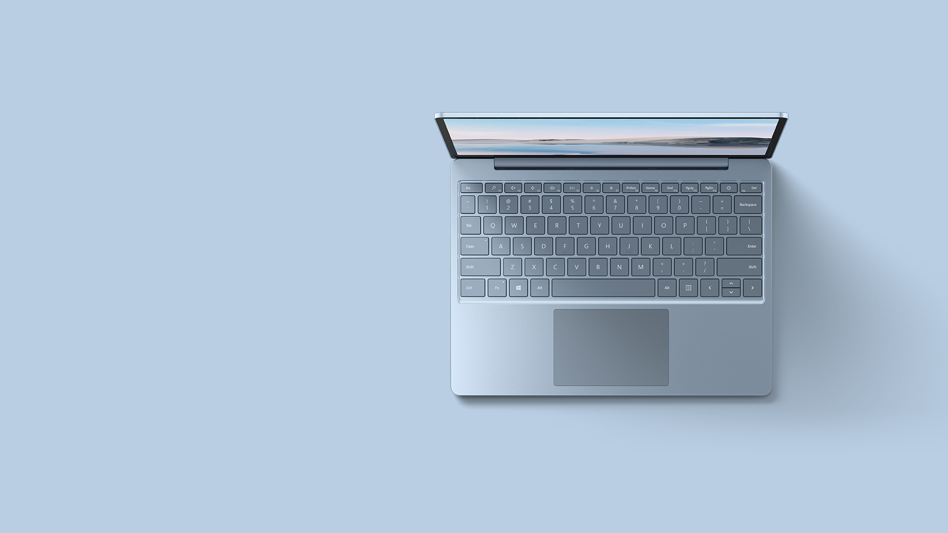 An aerial view of the ice blue Surface Laptop Go resting upon a matching background.