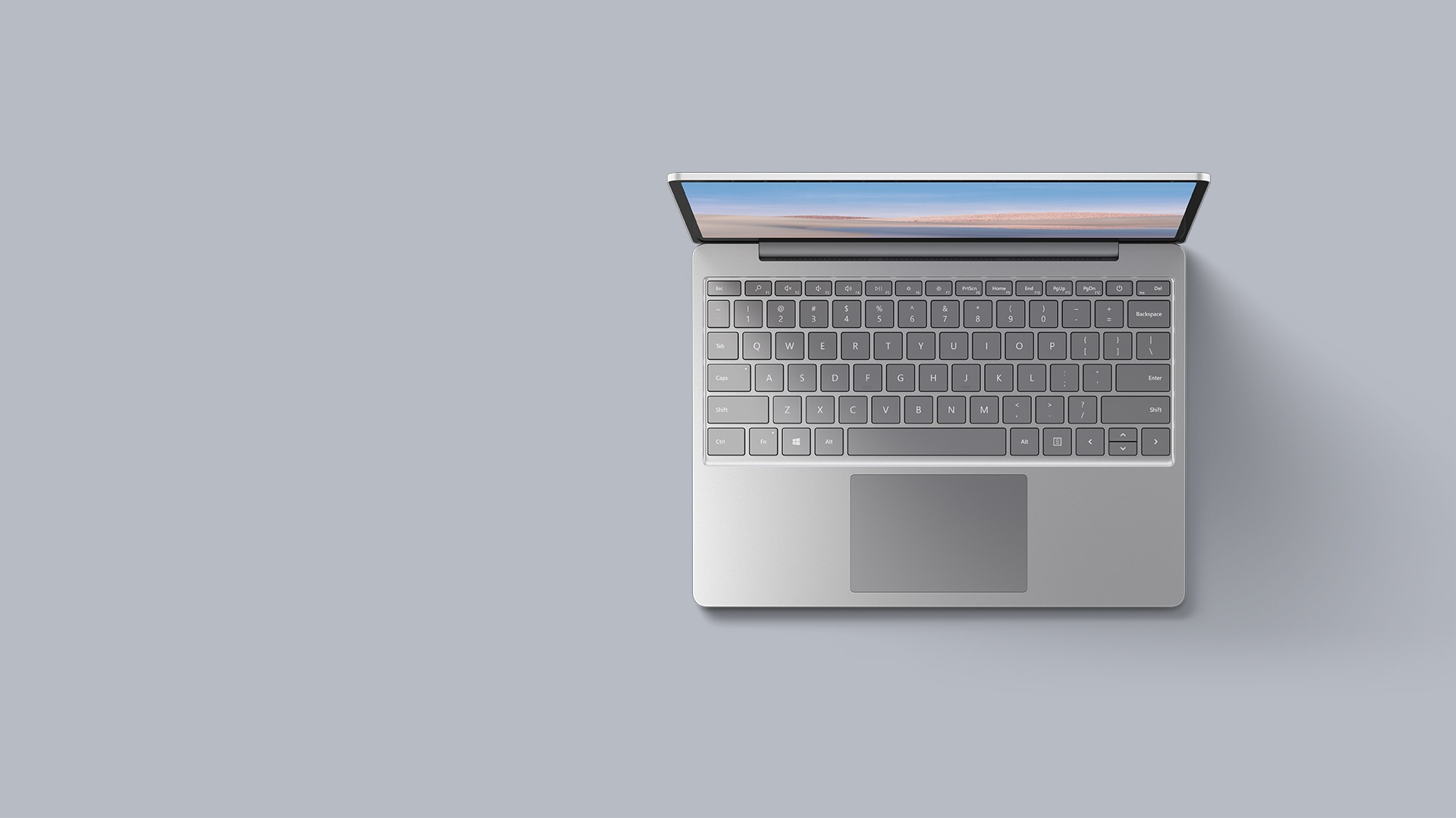 An aerial view of the platinum Surface Laptop Go resting upon a matching background.