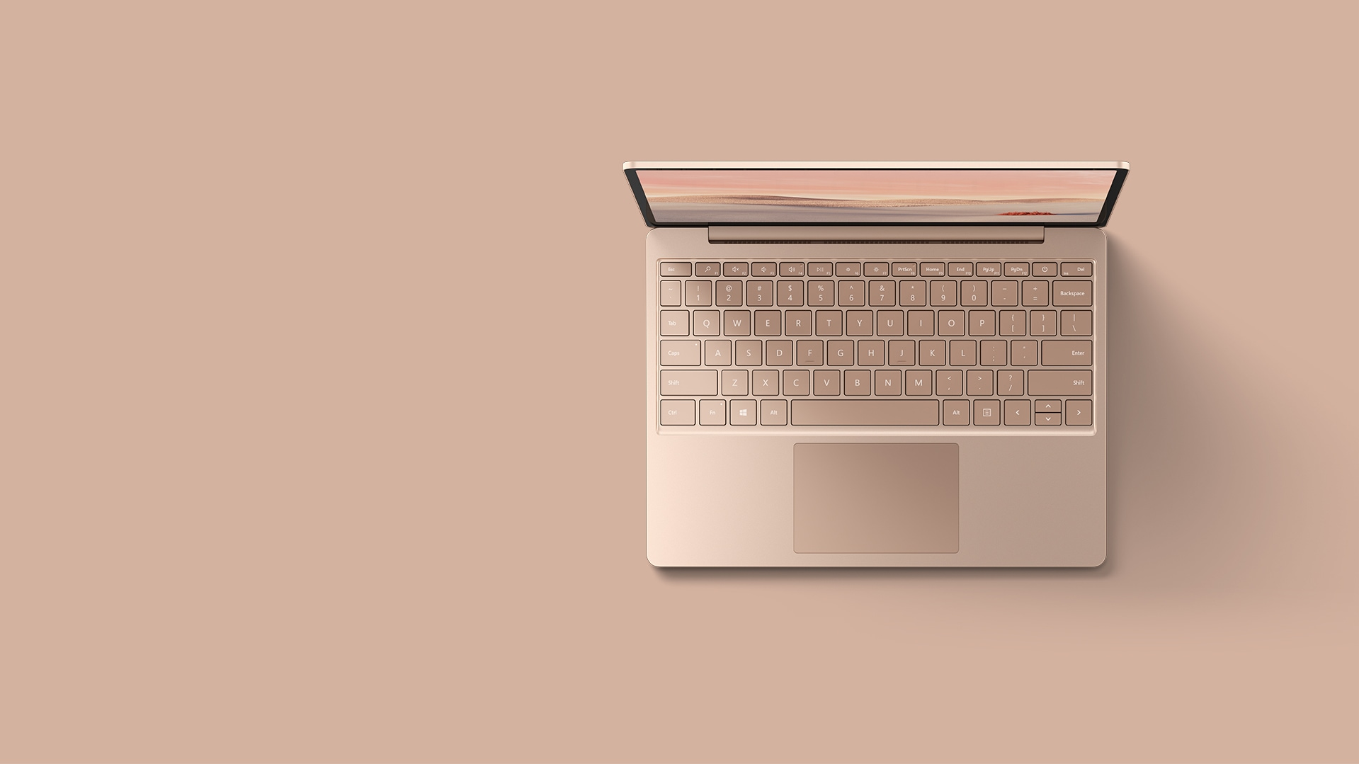 An aerial view of the  sandstone Surface Laptop Go resting upon a matching background.