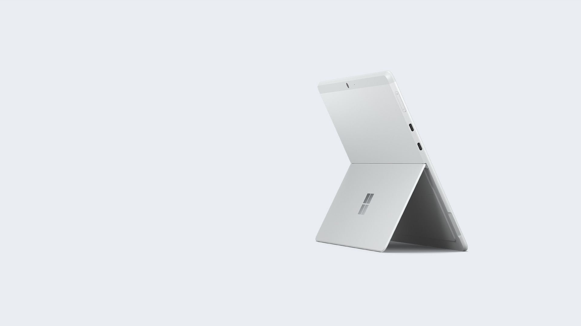 A Surface Pro X rests upon a stand against a platinum background.