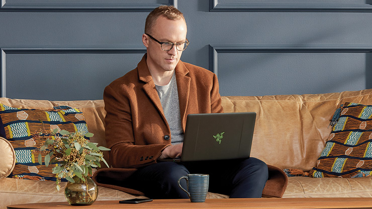 A man sits on a couch using a Razer laptop computer