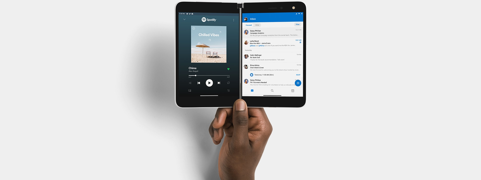 A hand holding up Surface Duo with Spotify & Outlook