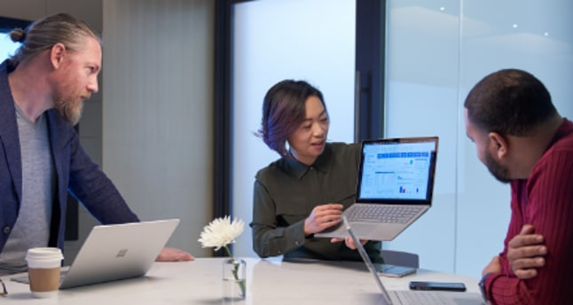 Three people working in a meeting room all with Surface laptops. One person is holding up their laptop and presenting the screen to the other two people.