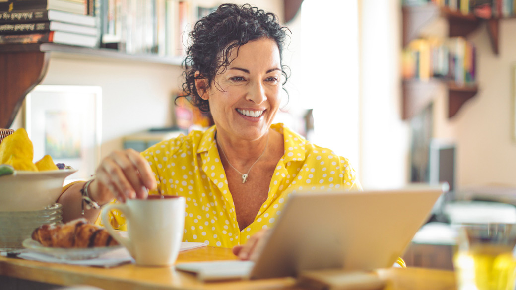 Smiling woman using laptop while having breakfast at her kitchen table.