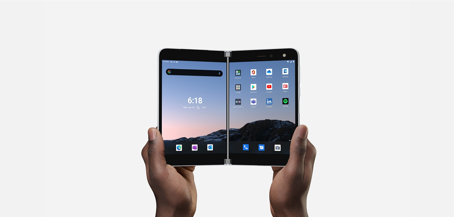 A pair of hands hold up Surface Duo in compose mode showing the home screen