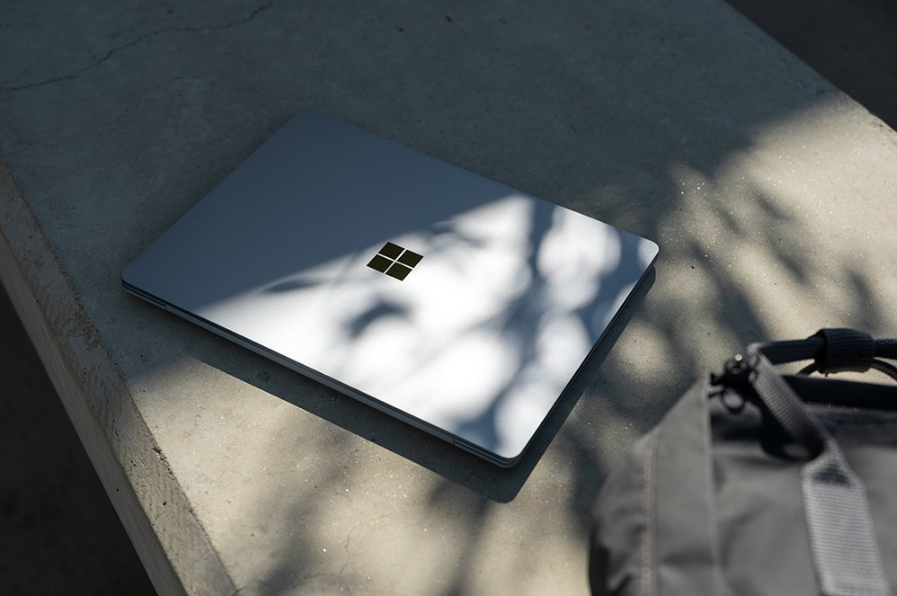 A Surface Laptop Go sits closed upon a concrete bench with a backpack nearby.