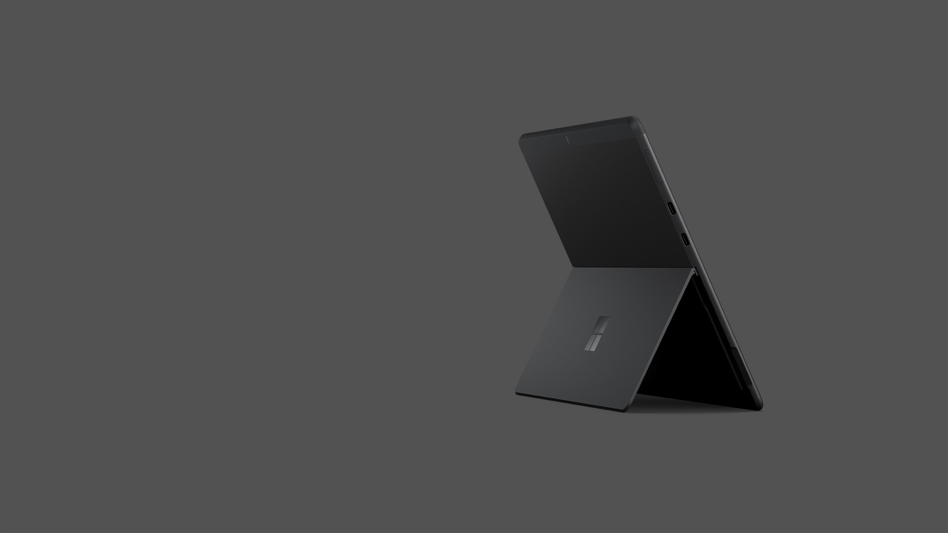 A Surface Pro X rests upon a stand against a black background.