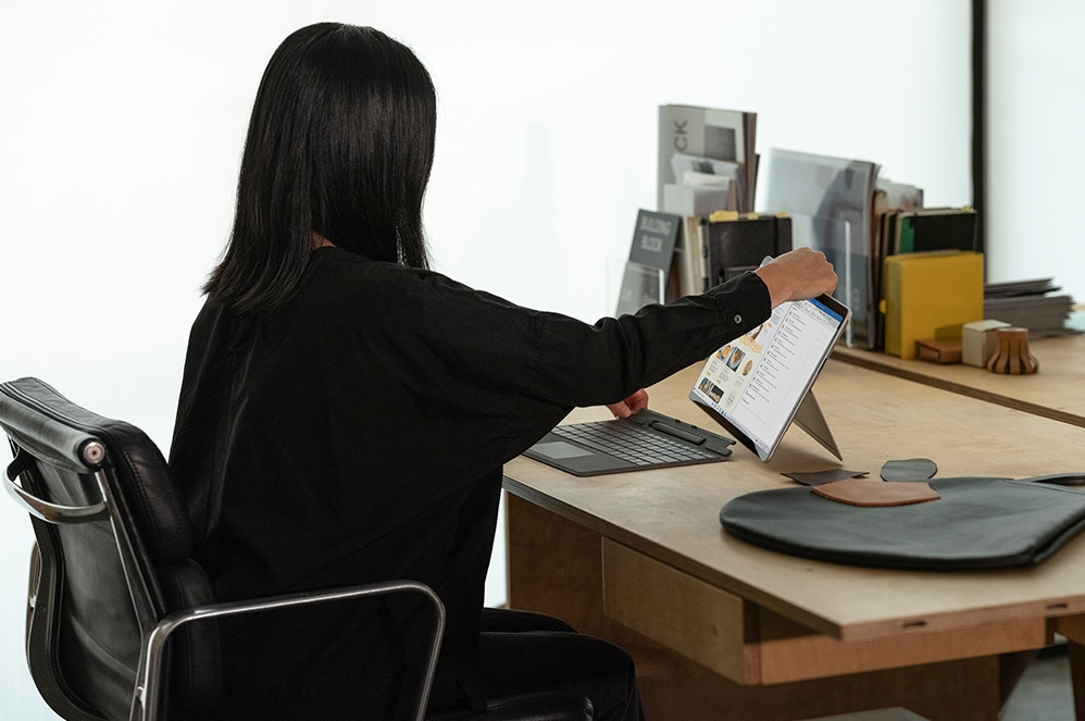 A woman connects her Surface Pro X to the Pro X Signature Keyboard with Slim Pen Bundle upon her work desk.