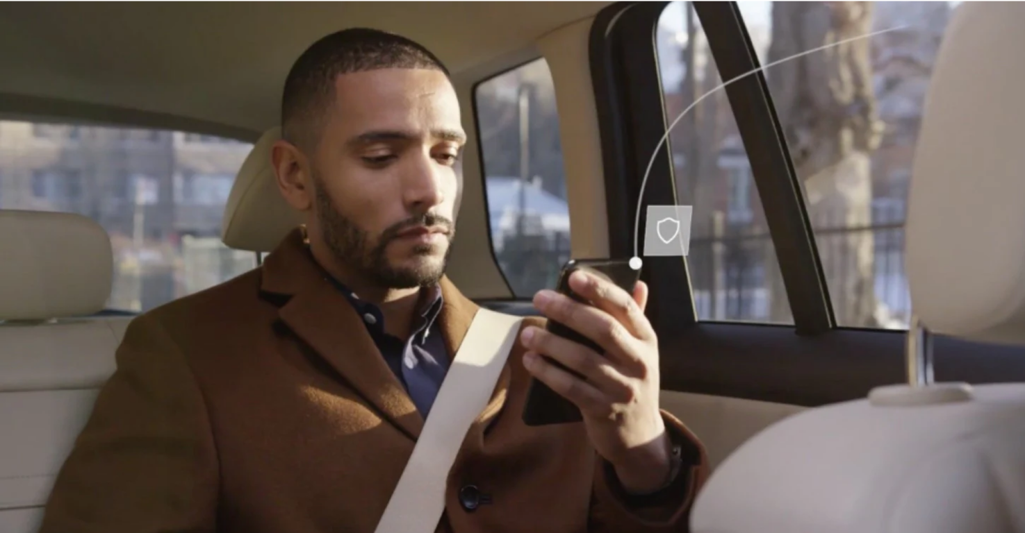 Photograph of a person sitting in the back seat of a car looking at a smartphone screen.