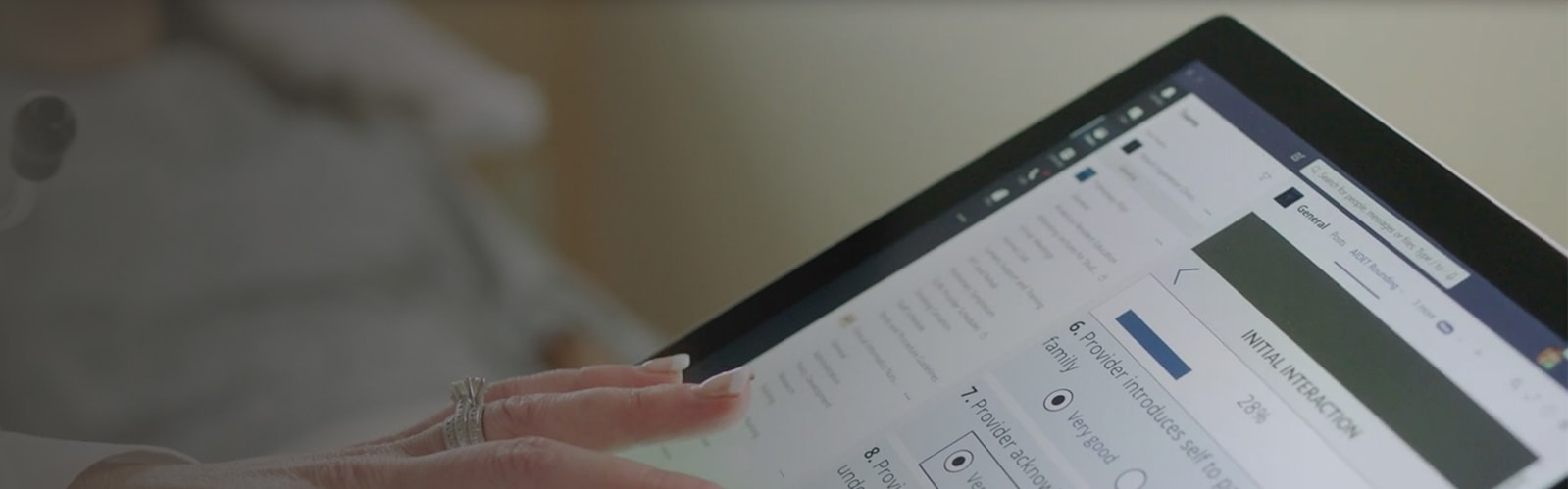 A person's hand touching a tablet device screen that shows a healthcare intake form.