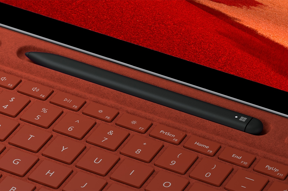 An image of the touchscreen pen resting in its designated place on the poppy red Surface Pro X Signature Keyboard with Slim Pen Bundle.