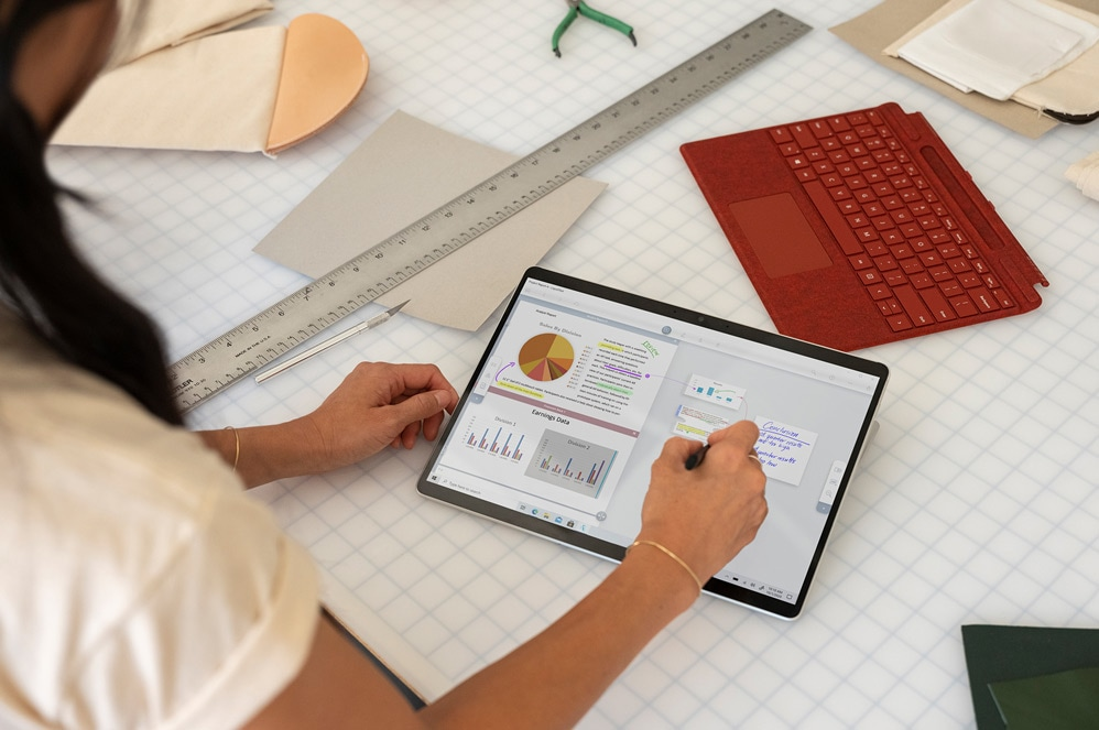 Surface Pro X held in tablet mode with Slim Pen by a person using Microsoft Word
