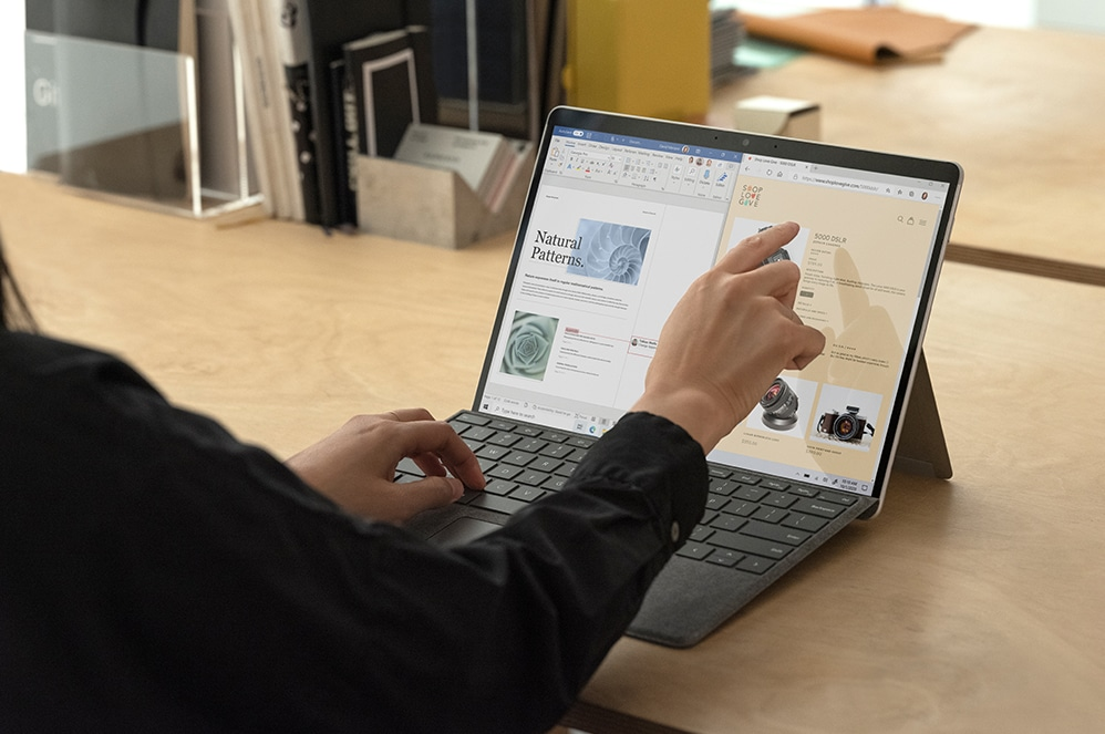 A person uses the touchscreen capabilities of their Surface Pro X with the keyboard and prop stand on a work desk.